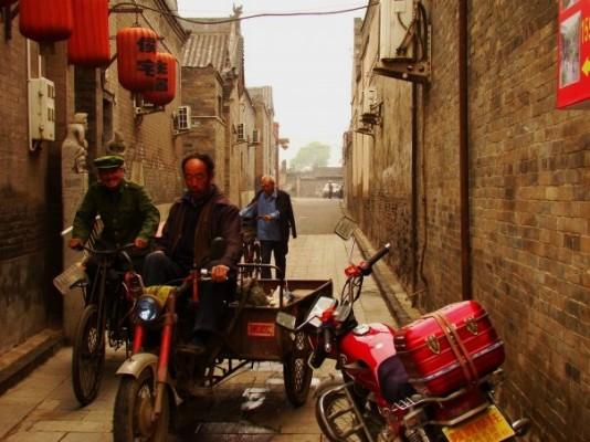 Men on Bike Carts in a Narrow Alleyway