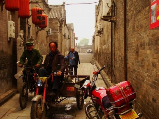 Men on Bike Carts in a Narrow Alleyway